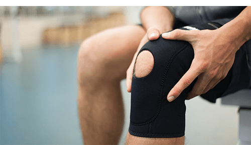 Person holding knee with brace on it