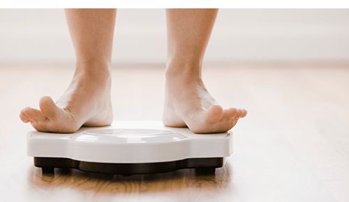 Person weighing themself on scale