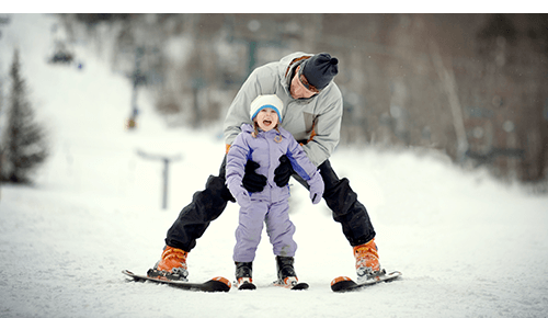Parent helping their child learn how to ski on a snow covered mountain