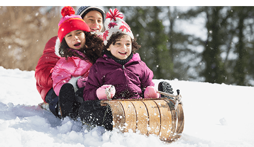 Three children on sled riding down snow covered hill