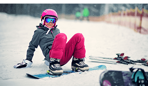 Child sitting on the snow covered grown with a snowboard attached to their boots