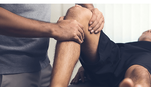 Sports medicine doctor assessing running injury on a person's knee while they on an exam table