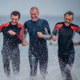 Group of men wearing wetsuits while running out of a body of water