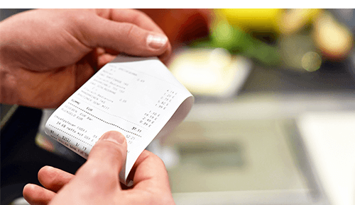 Hands holding a store receipt