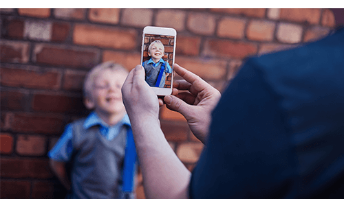Person taking a picture of a child with their smart phone