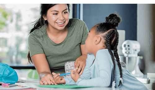 Young adult talking too a child while they color