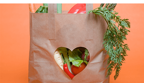 Brown paper bag full of vegetables with a heart shape cut out in the front of the bag