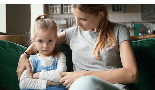 Woman talking to an upset looking child while sitting on a couch