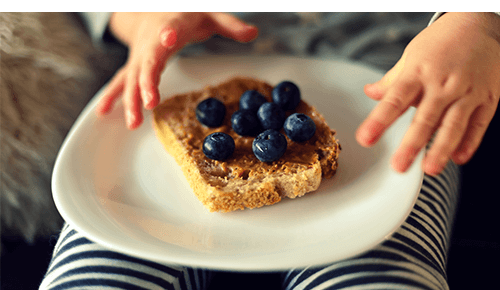 Child with a piece of toast with peanut butter and blueberries on top