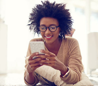 Woman laying on the floor looking at her phone while smiling