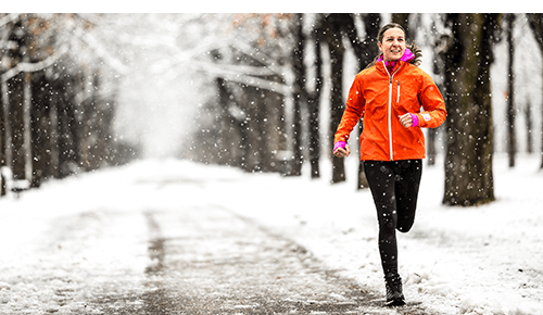 Woman running outdoors during the winter on a snow covered path