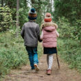 Children walking together down forest trail