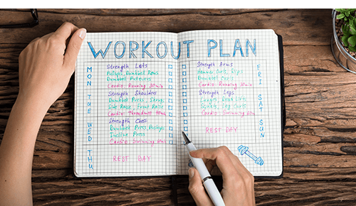 Person writing in journal with a workout plan written on the pages