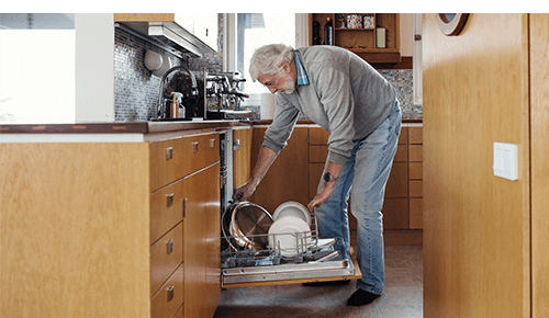 Older Man Loading Dishwasher