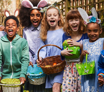 Group of children with Easter clothing on holding Easter baskets