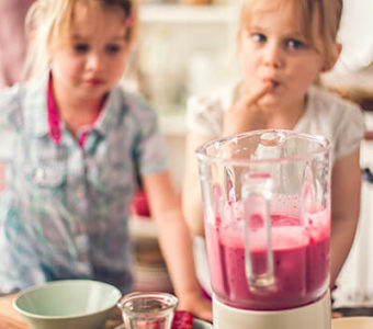 Two children helping make a pink smoothie in a blender at a kitchen counter