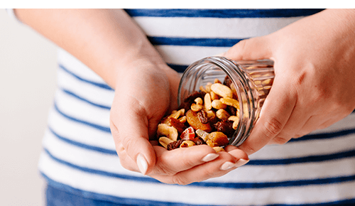 Person pouring mixed nuts into their hand from a jar