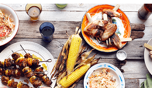 Tabletop view of a variety of grilled foods during a cookout