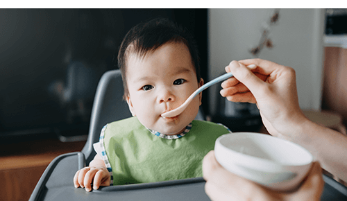 Person feeding baby in a high chair