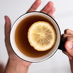 Closeup of person holding a mug full of tea with a lemon slice