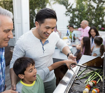 Multiple generations of family cooking food on a grill outdoors