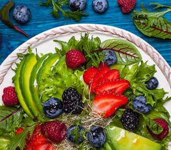 Plate of salad topped with avocado and mixed berries