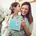 Daughter giving her mother a gift bag for Mother's Day