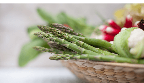 Closeup of asparagus spears in a basket full of vegetables