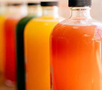 Glass bottles lined up in row and filled with different types of pressed juices