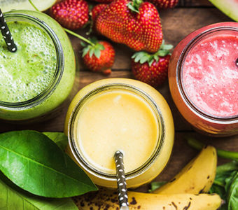 Birds-eye view of three different fruit smoothies in glass cups surrounded by a variety of fresh fruit