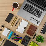Desktop with variety of office tools and laptop computer