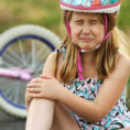 Young girl sitting next to bike crying and holding hurt knee