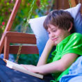 Child reading a book on a porch swing outside