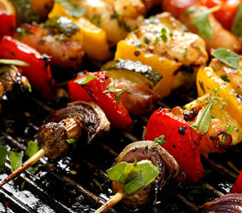 Meat and vegetables on a skewer sitting on a grill