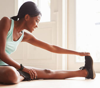 Woman stretching her legs on floor after exercise
