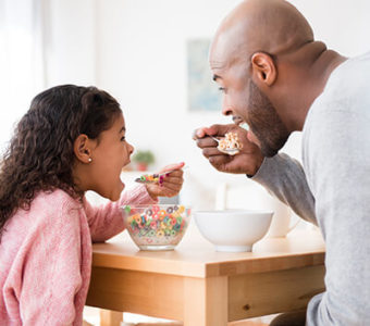 Father and child eating cereal together at kitchen table