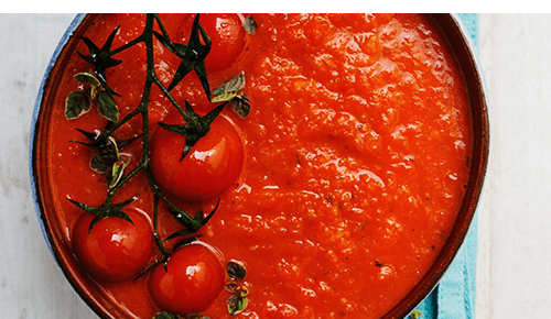 Pot of tomato sauce with whole fresh tomatoes sitting on top