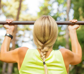 Woman doing pull-ups on an outdoor metal bar