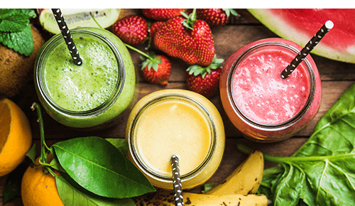 Three glass mugs filled with different fruit smoothies surrounded by fresh fruit