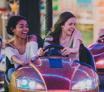Two laughing young adults in a bumper car with another group in the background