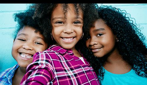 Three children smiling into camera