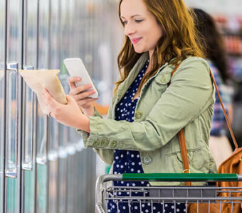 Woman using phone to check nutrition facts on food packaging in a grocery store aisle