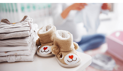Baby shoes and clothing sitting on dresser with pregnant person looking through clothing in the background