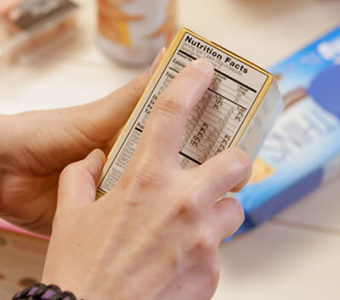 Closeup of person reading the nutritional label on a food container box