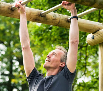 Man exercising on bars in outdoor workout area
