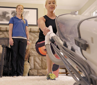 Woman exercising while vacuuming with guidance from an exercise physiologist