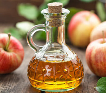 Small bottle of apple cider vinegar surrounded by apples
