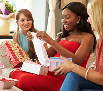 Group of people smiling as a pregnant person opens gifts at their baby shower