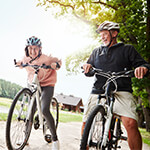 Couple riding bikes together on an outdoor path