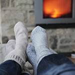 Two pairs of socked feet resting on a table in front of a fireplace